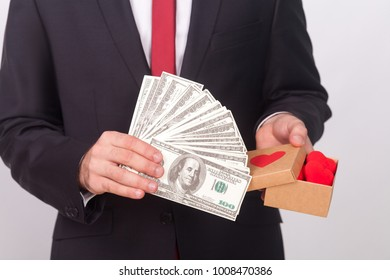 Love or money. Which is better, proposes man in suit. Indoor, studio shot, isolated on gray background