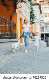 Love of mother and daughter. Happy woman and her  daughter walking around the city with dog. Street to school. Mothers day.