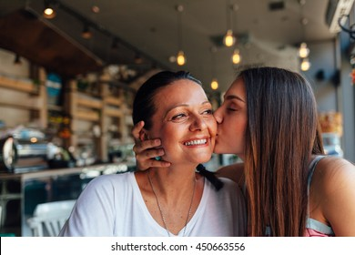 Love of mother and daughter. Happy women in a nice cafe with copy space on blurred background. Aged woman and her adult daughter drinking coffee at cafe. Mothers day.