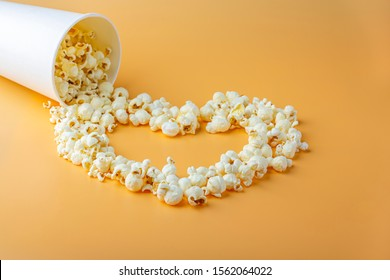 Love movies concept. Popcorn in paper box scattered on orange background heart shaped close up, copy space for text. Cinema snack concept. Popcorn box mocap