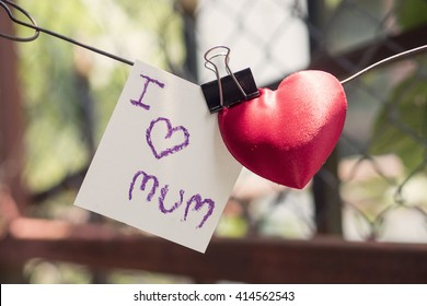I love mum messages and red heart hanged and blurred background with sunrise , mother's day concept