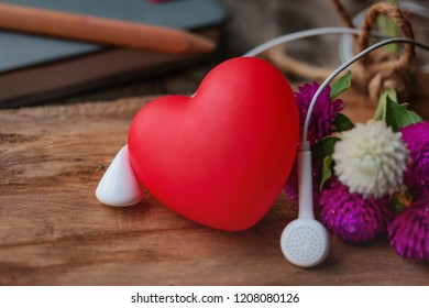 Love music concept. Red heart and earphones music and flowers on wooden desk in countryside.