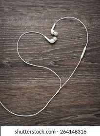 Love Music. Headphone wires in the form of heart on wooden background