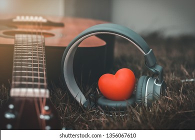 Love music. Red heart and headphones music and guitar in fields. Sound of life. Acoustic music and vintage style. Abstract listening song relaxing in the country.
