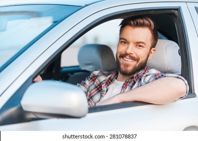 I love my car! Handsome young man driving his car and smiling at camera