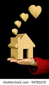 love my home, woman holding golden house with gold heart shapes as smoke from the chimney