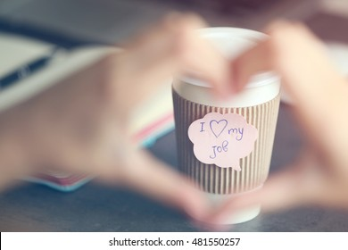 I love my job concept. Female hands in heart shape and cup of coffee