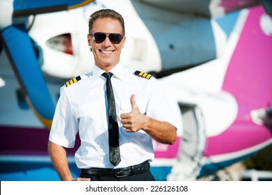 I love my job! Confident male pilot in uniform showing his thumb up and smiling while standing in front of the airplane