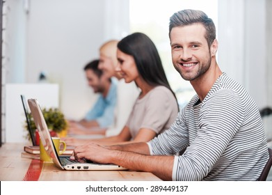 I love my job! Group of cheerful business people in smart casual wear working at their laptops while handsome man looking at camera and smiling