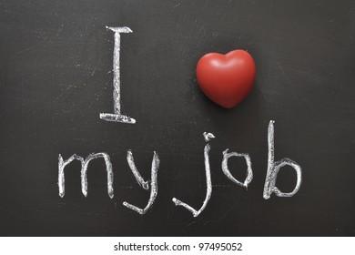 I love my job -  positive concept handwritten on black chalkboard with volume red heart symbol
