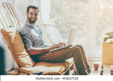 I love my job! Side view of smiling young man working on laptop and looking at camera while sitting in the rest area of the office