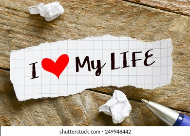 I love my life Note. Note with I love my life and red heart on the wooden background with pen