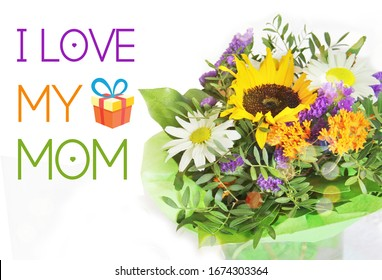 I love my mom greeting card on white background and beautiful  flowers bouquet with sunflower and camomile