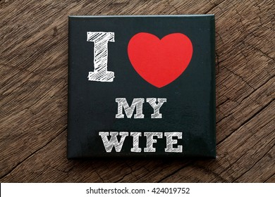 I Love My Wife written on black note with wood background