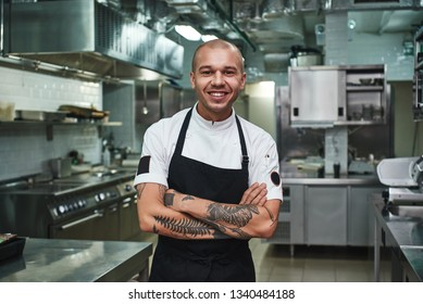 I love my work Cheerful young chef in apron keeping tattooed arms crossed and smiling while standing in a restaurant kitchen