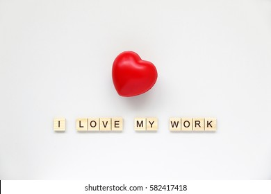 I LOVE MY WORK text word made with wood blocks and Red Heart on table White.