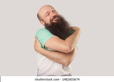 I love myself. Portrait of happy middle aged bald man with long beard in light green t-shirt standing hugging himself smiling and enjoying. indoor studio shot, isolated on grey background.