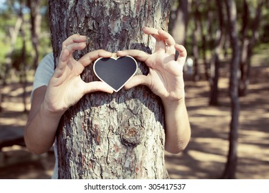 Love of nature / Female hands hugging tree with heart shape