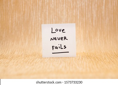 Love never fails - card with lettering on glitter gold background, christian biblical phrase