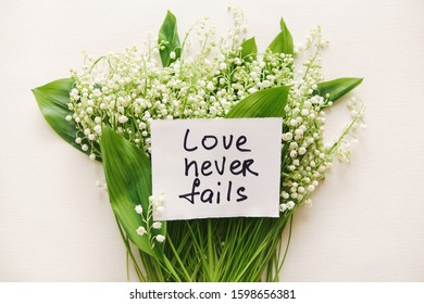Love never fails - card with lettering and bouquet of flowers, biblical verce and religion concept