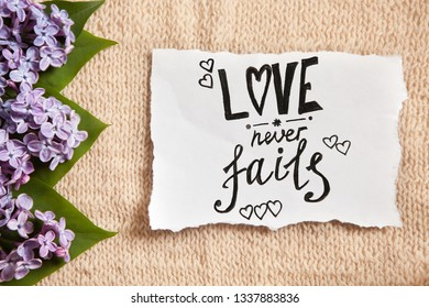 Love never fails - pink flowers and calligraphy text on paper, bible quote