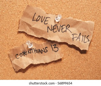 Love Never Fails written on scraps of wrinkled brown bag pinned to a corkboard