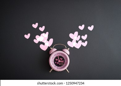 It's love o'clock. Valentine's pink alarm with heart shaped symbols on black leather background