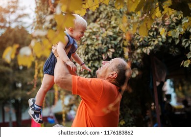 Love on first sight. Proud grandfather playing with is grandson in a backyard, lifting him in the air.