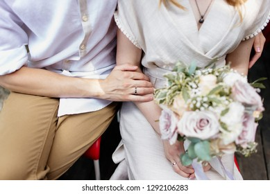 Love on wedding day. Caucasian bride and groom hugging and holding a colorful wedding bouquet in their hands.