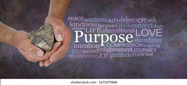 Love is our True Soul Purpose - male hands holding a wooden love heart beside a PURPOSE word cloud against a rustic dark purple brown stone grunge background