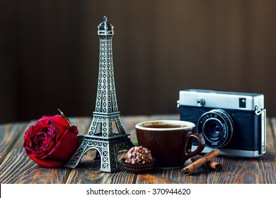 Love Paris! Rose, vintage camera, Eiffel tower, coffee cup, chocolate and cinnamon sticks on wooden background. St Valentine's Day concept. Nostalgic holidays background