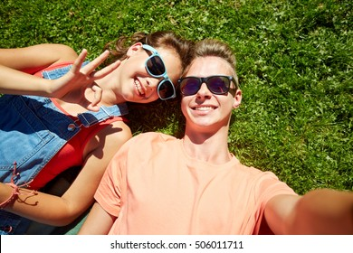 love and people concept - happy teenage couple in sunglasses lying on grass and taking selfie at summer