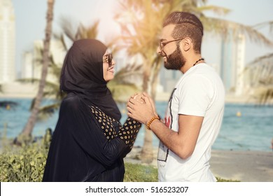love and people concept - happy teenage arabic couple in sunglasses hanging on beach background at summer, Abaya and Hijab dress