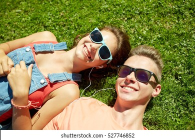 love and people concept - happy teenage couple in sunglasses lying on grass with earphones and listening to music at summer