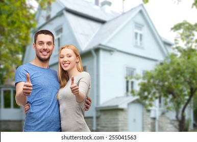 love, people, real estate, home and family concept - smiling couple hugging and showing thumbs up over house background