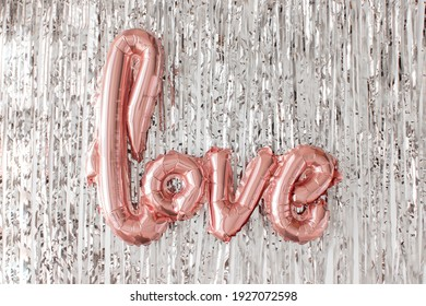 Love pink foil balloon on silver tinsel flat lay. Valentines day, wedding celebration. Metallic shiny letters. Romatic party. Love sign. Fashion decor