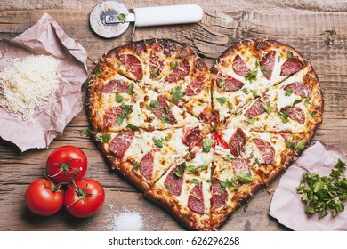 Love pizza. Baked heart-shaped homemade pizza on a cutting board on white wooden background. Close up