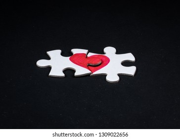 Love puzzle. Pieces of a puzzle with half of a red heart drawn on each piece, fitting perfect together. On black background.