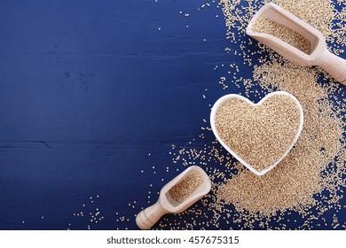 I love quinoa concept with white grain quinoa in white heart shaped bowl on a dark blue wood background.