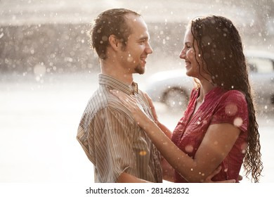 Love in the rain. couple in love hugging and kissing under summer rain