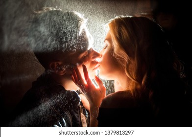 Love in the rain .Silhouette of kissing couple under umbrella. Night photo in the lights