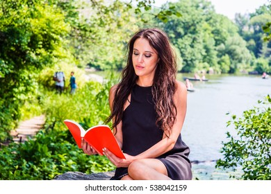 I Love Reading. American woman with long black hair, wearing black dress, sitting on rocks by lake at Central Park, New York, in summer, holding red book, reading. Color filtered effect.