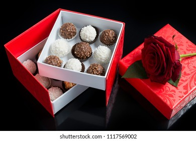 Love red chocolate box open with reflection and fully bloomed rose on black background