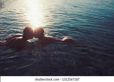 Love relations of naked couple in sea water. Summer holidays and paradise travel vacation. Couple in love with sexy body relax on beach. Sexy woman and man have sex games. Family and valentines day.