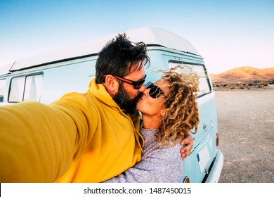 Love and relationship concept with couple of traveler with old vintage van kissing and taking a selfie picture -alternative lifestyle and. vacation with beautiful woman and man outdor