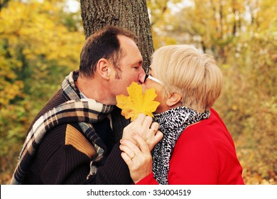 Love, relationship, family, age, tourism, travel and people concept - close up of couple kissing in autumn park