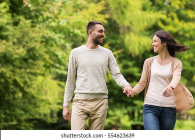 love, relationship, family and people concept - happy couple walking in summer park