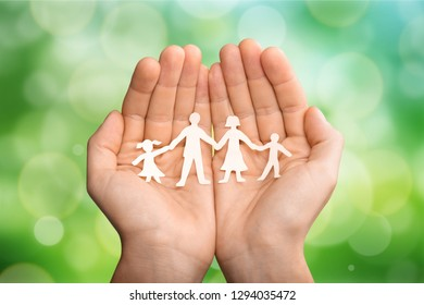 Love and relationships concept - closeup of man's cupped hands showing paper  family