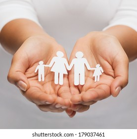 love and relationships concept - closeup of womans cupped hands showing paper man family