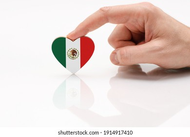 Love and respect Mexico. A man's hand holds a heart in the shape of the Mexico flag on a white glass surface. The concept of Mexican patriotism and pride.